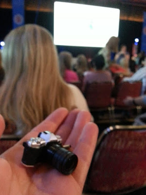 Miniature camera displayed on an open hand in a conference hall.