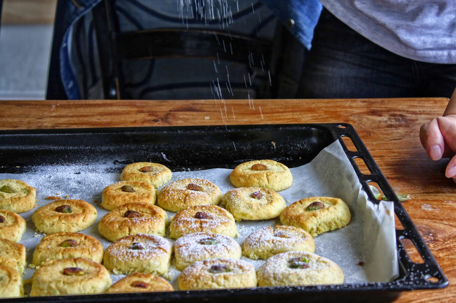 sifting icing sugar on the thumbprint cookies
