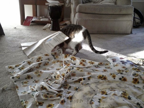 Cat burrows her head into a sheet of sewing directions, next to a length of sunflower fabric that is spread out on the ground with pattern pieces pinned to it.