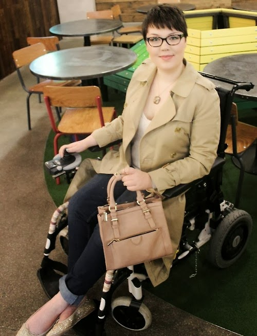Photo of a young woman with short brown hair and glasses, wearing a tan trench coat and business attire, sitting in an electric wheelchair