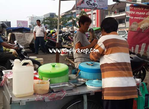 Penjual Air Tahu sedang sibuk melayani pelanggan setianya. Foto Asep Haryono