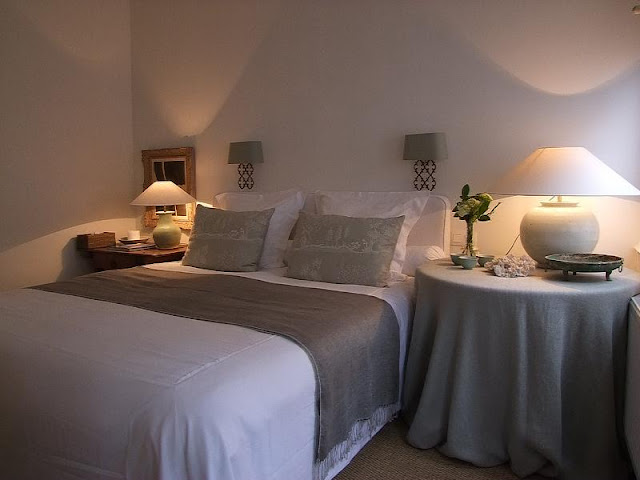 subdued colors and soft lighting make the master bedroom on the