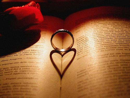 Aliança formando sombra em livro, aliança forma imagem de coração