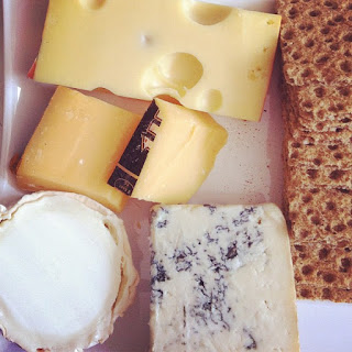 A platter containing four types of cheese, and crackers.