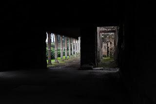 Ingresso esterno e uscita interna verso giardini, di un antico tempio abbandonato, che passano in uno stanzone buio