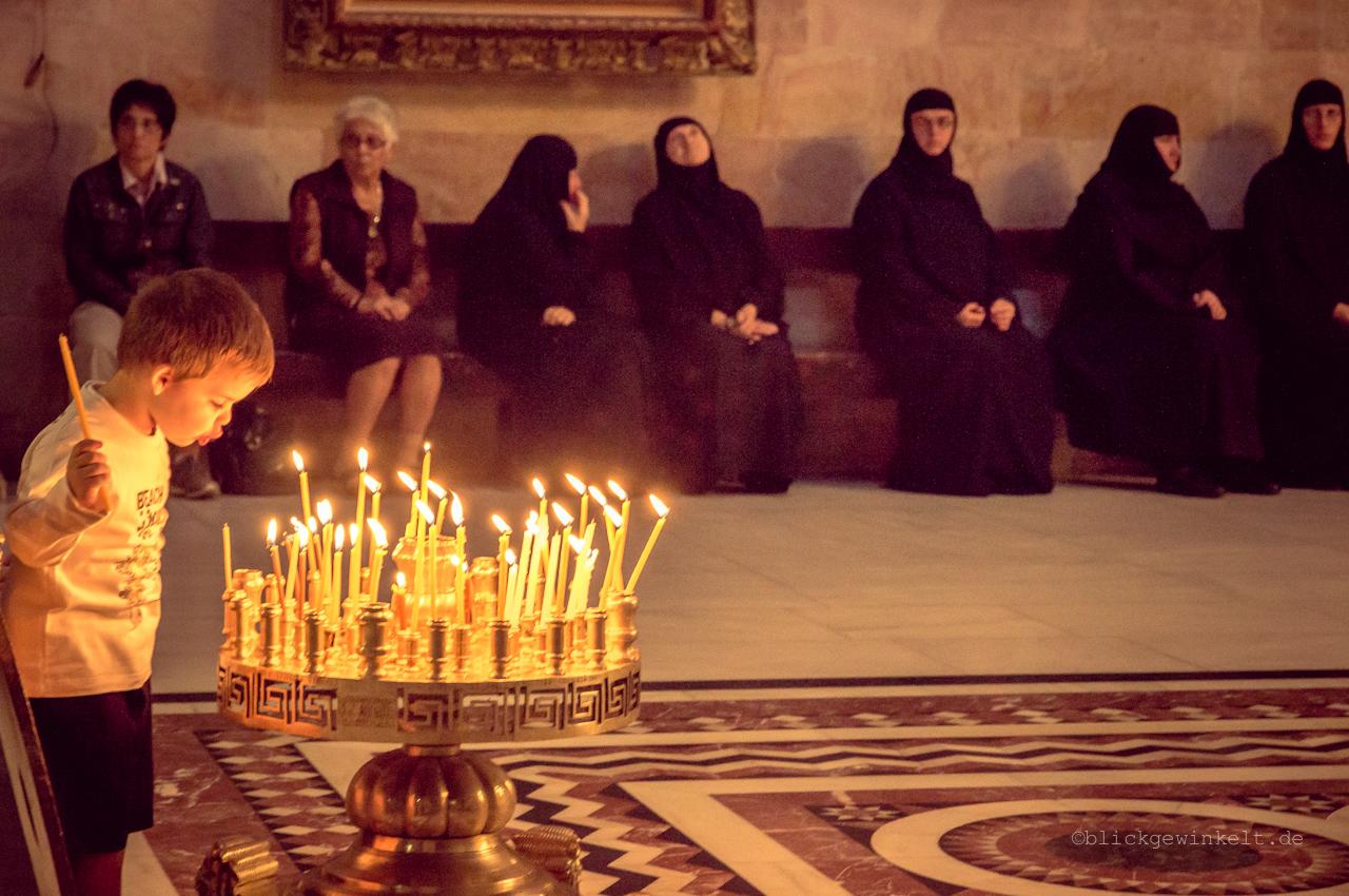Kleiner Junge bläst Kerzen einer Messe aus
