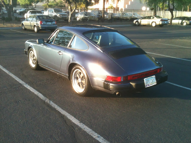 Rear 3/4 view of  purple 1986-1989 Porsche 911 parked in parking lot