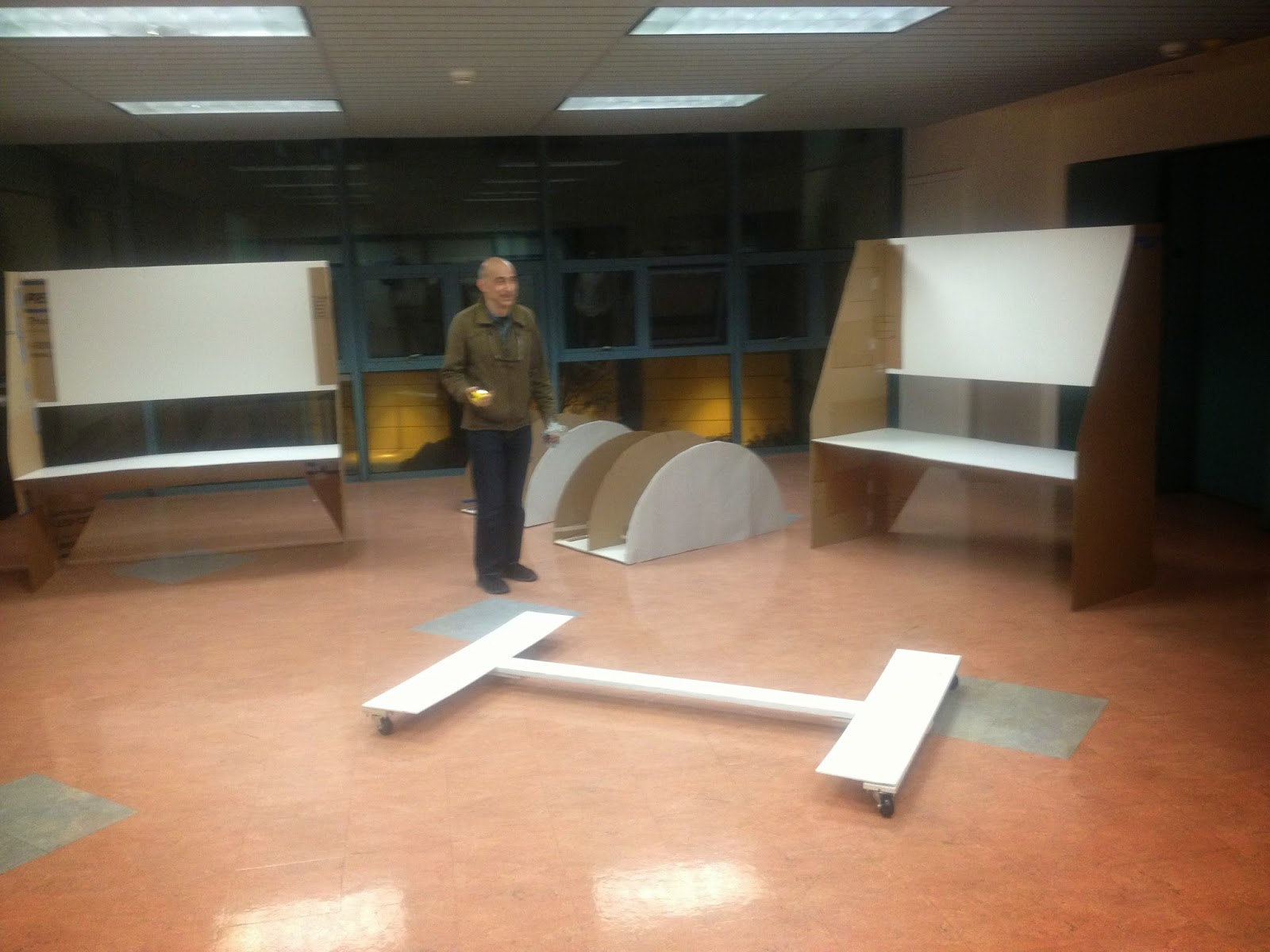 The dolly sits in front of the image with other cardboard model pieces standing in the background. The instructor stands at the center inspecting the pieces.