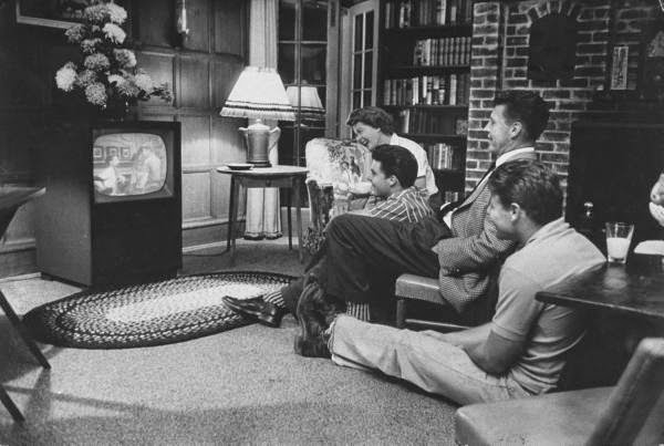 The Nelson family gather around the TV to watch an episode of their show. 1959.