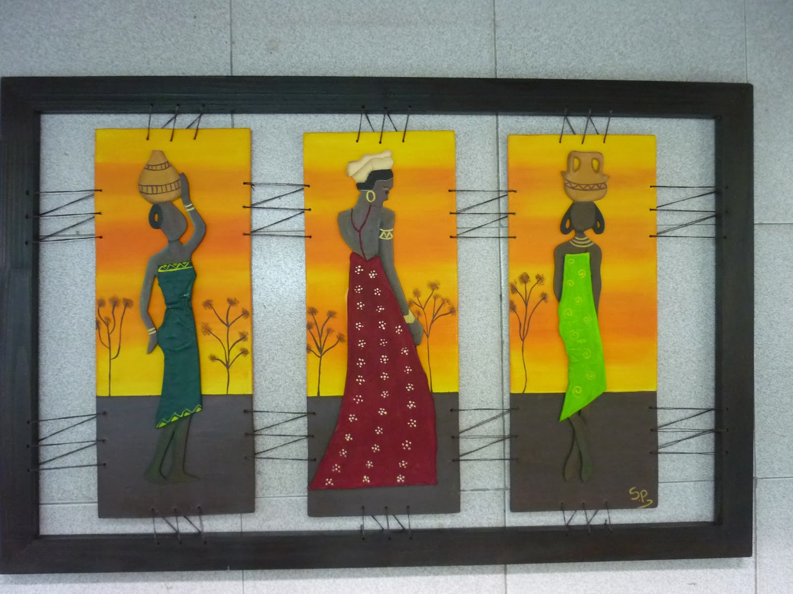 triptico de africanas realizadas con tela endurecida sobre un fondo pintado al acrilico de un paisaje las tres maderas atadas a un marco chato con rafia