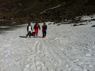 La imagen muestra a dos alumnos andando hacia arriba y a una profe tirando del trineo.
