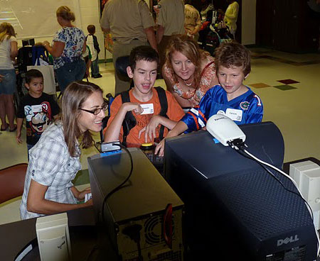 Photo from AbleGames of a young lad playing a one-switch game amongst friends and family.