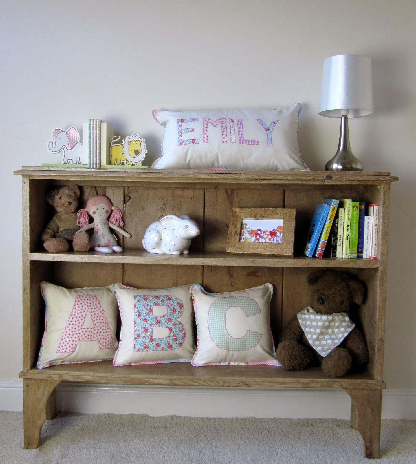 nursery shelves with monogrammed pillows