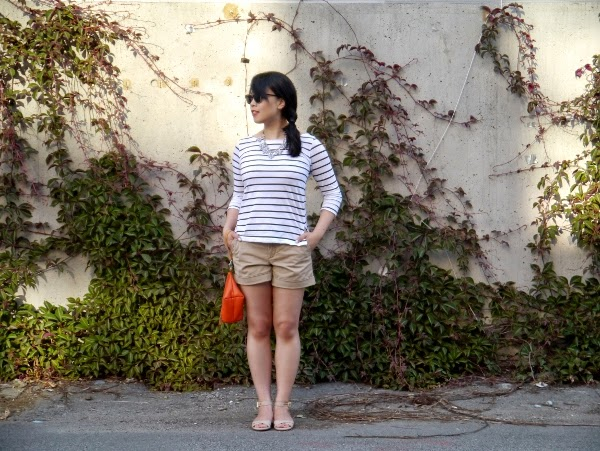 Black and white Breton striped top, statement necklace, khaki shorts, ankle strap mini espadrille wedges, orange wristlet