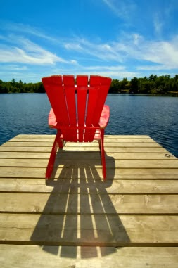 red wooden lounge chair perched on the edge of a lake dock on a sunny summer day