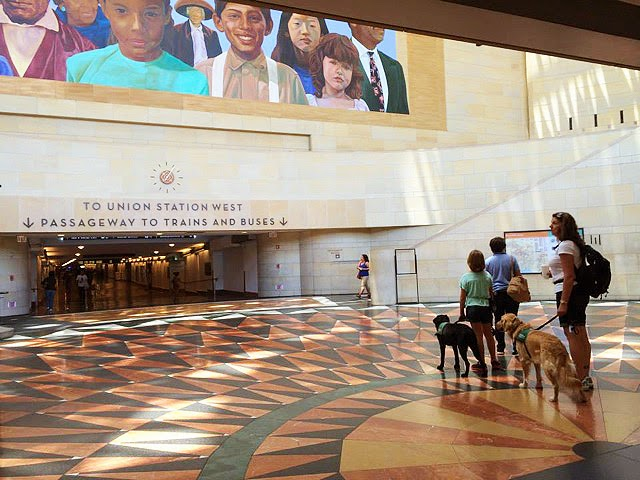 "Puppy raisers with a black Lab and golden Retriever puppy stand near the signs that say ""To Union Station West"" the floor is a colorful intricate pattern and the mural above is of children of different ethnicities."