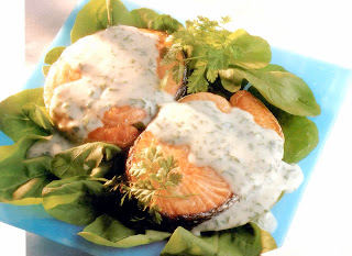Salmon steaks served on a bed of lettuce and drizzled with a cheesy herb sauce
