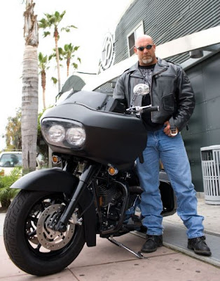 Goldberg standing along his black bike