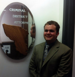 Lange poses in front of Austin District Attorney's sign.