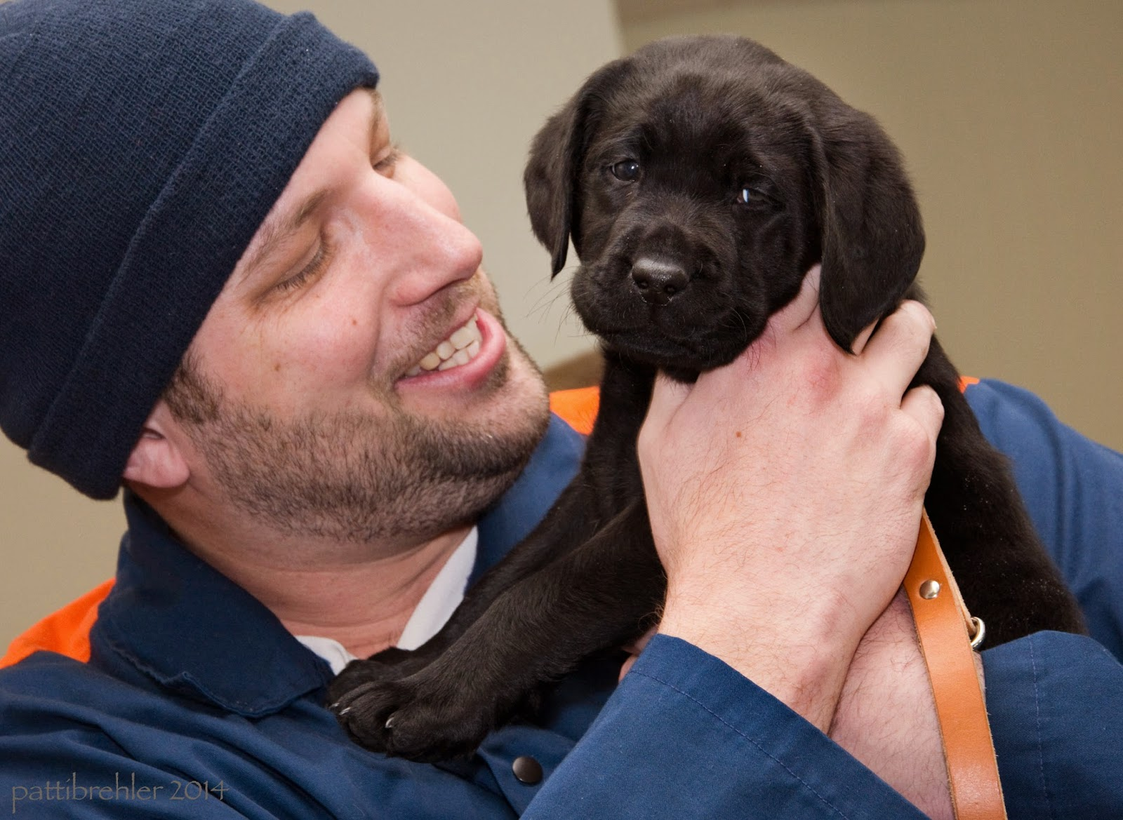 A close up shot of the man and the puppy. The puppy is looking sweetly at the camera and being held in the man's arms. The man's right hand is holding the puppy securely. The man is smiling and tooking at the puppy. The puppy's front paws are resting onthe man's upper chest.