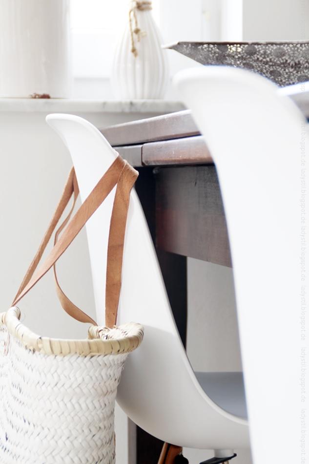 Herbstimpressionen Eames Stuhl mit Korbtasche vor dunklem Tisch mit Herbstdeko