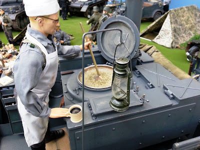 1/6 scale German soldier stirring soup in a diorama of an army post on display at a scale model exhibition.