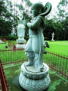 Estátua de pedra de um monge em posição de reverência.