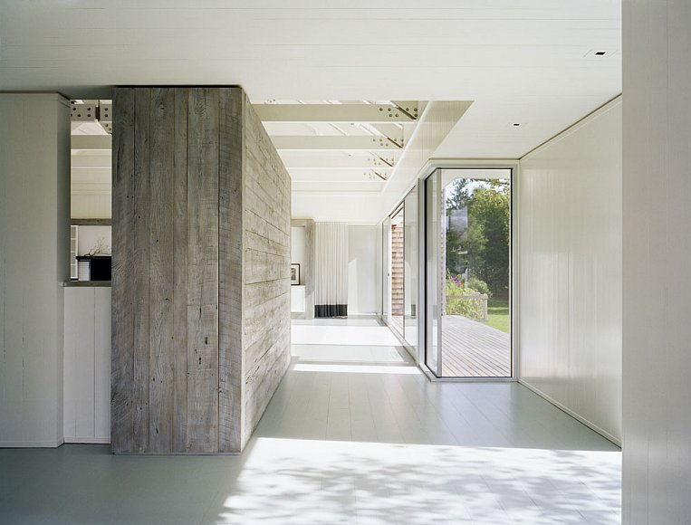 Hallway in a Montauk on Long Island lake house with large picture windows and a reclaimed wood wall