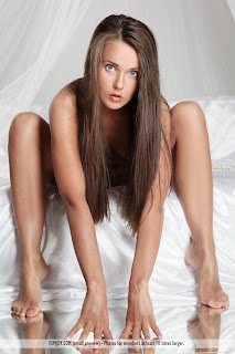 "Benita - ""Thinking of You"" by Femjoy (AKA Chantelle A, Anastasia Petrova) nude girl with brown hair and blue eyes sitting on bed bent over touching floor"