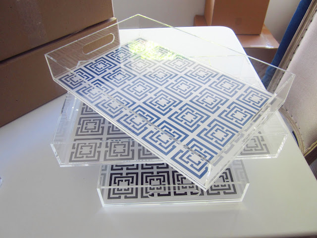 Two black and one blue COCOCOZY Logo Lucite Trays being packed for shipping