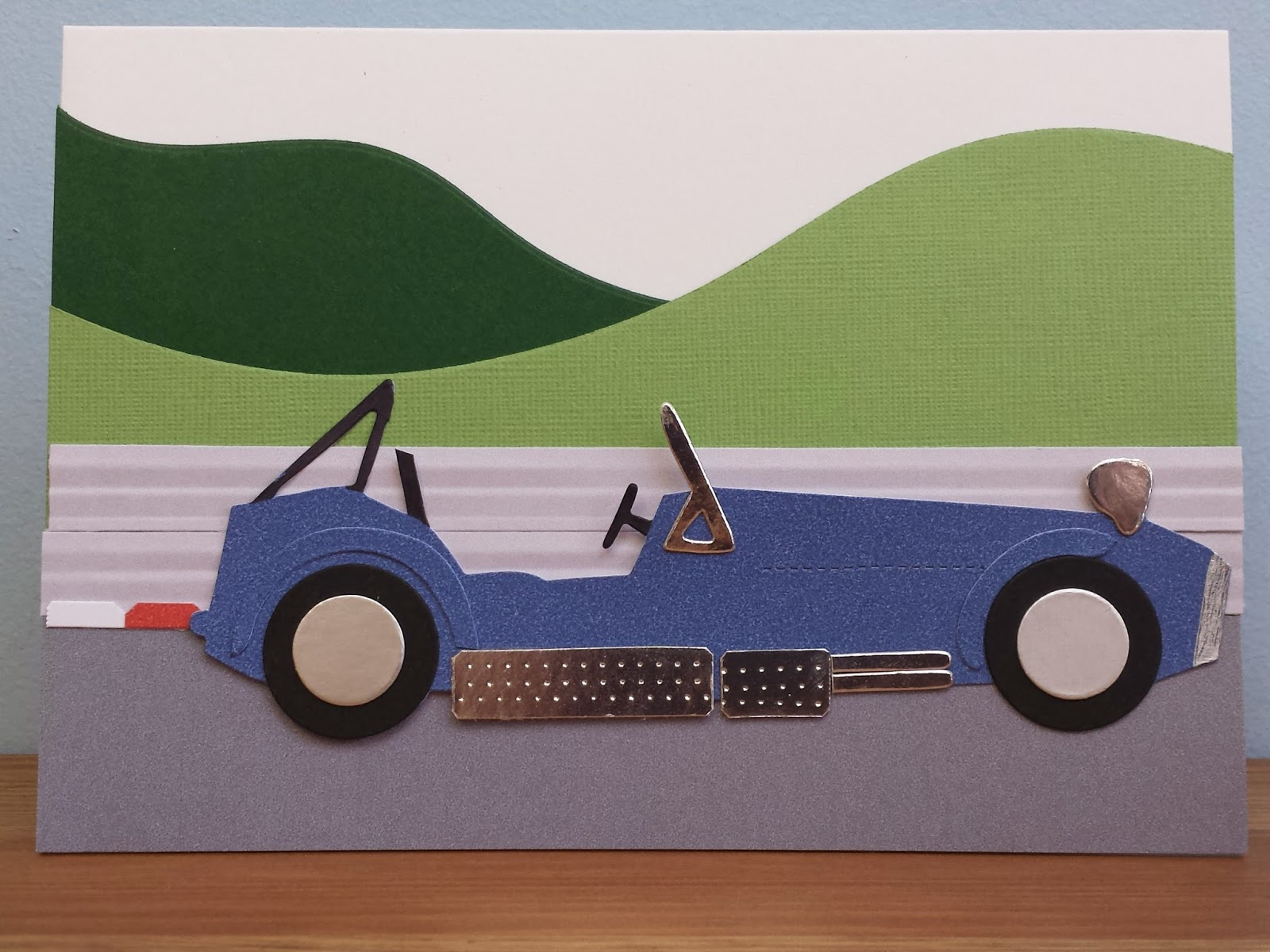 Caterham Card with multiple primaries, cat and exhaust cover and track background.