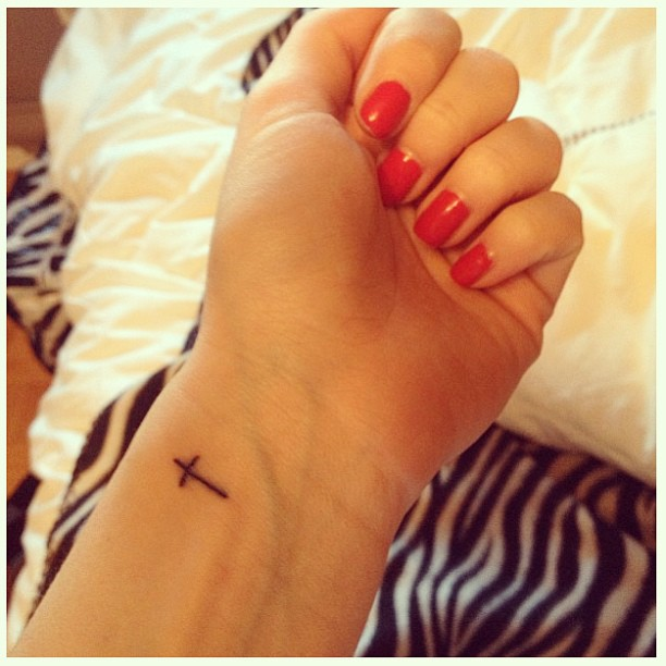 small cross tattoo on side of wrist