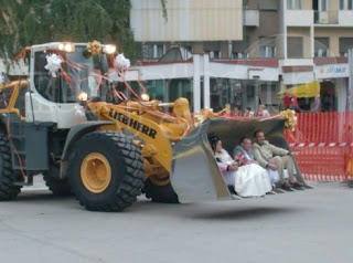 funny wedding picture: newlyweds in the bulldozer