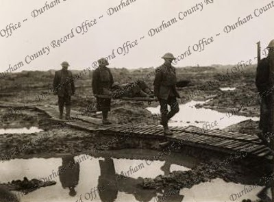 Ministry of Information photograph of British soldiers carrying a wounded man, on a stretcher, across a battlefield near Ypres, Belgium, 15 February 1918 (D/DLI 2/8/61(13))