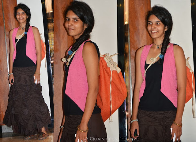 Black camisole with brown full length skirt, a bright pink waistcoat, and an orange jute bag.