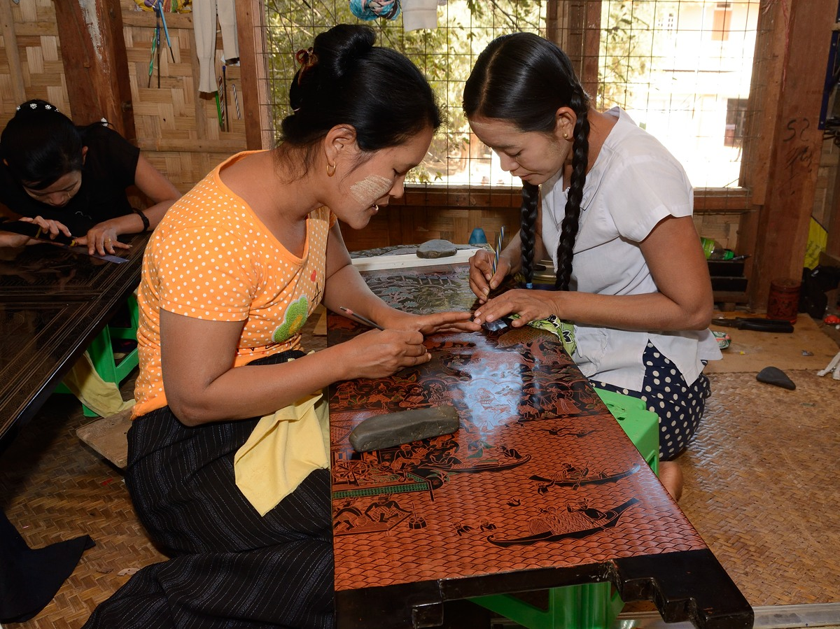 Woman carving design into lacquerware