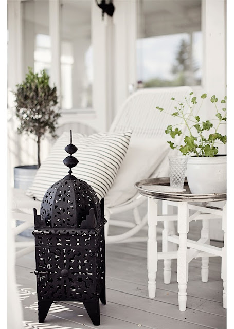 Black Moroccan lantern lamp on a grey front porch