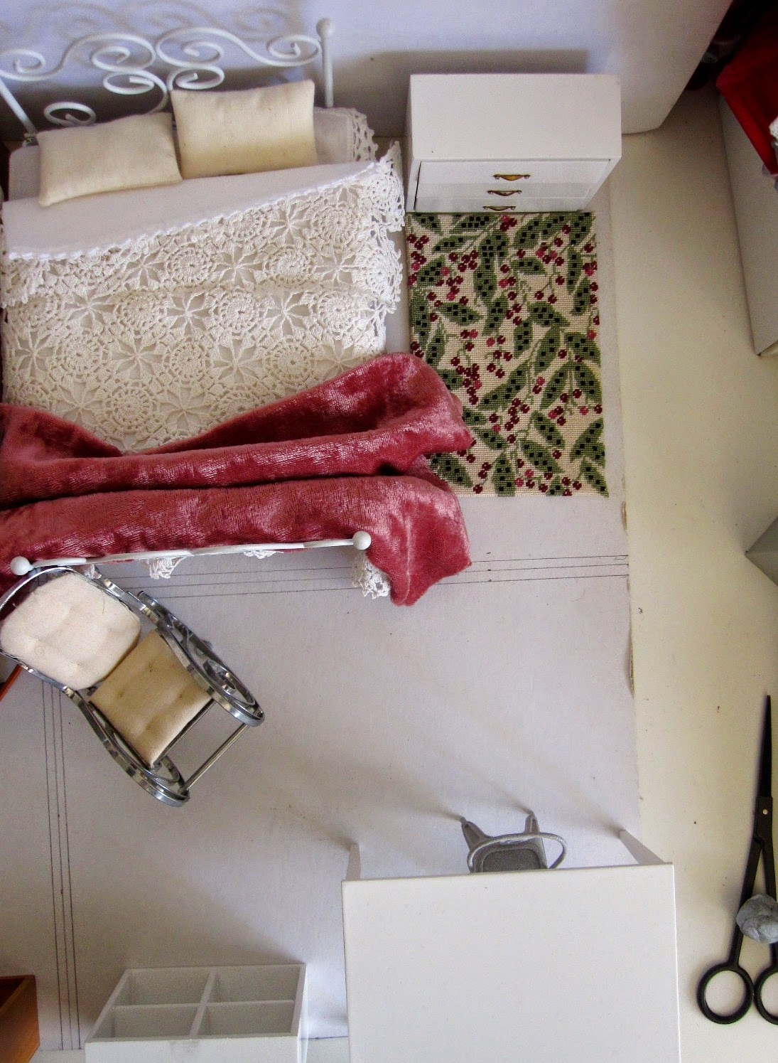 View from above of shabby chic dolls' house miniature furniture bedroom setting arranged on a piece of cardboard.