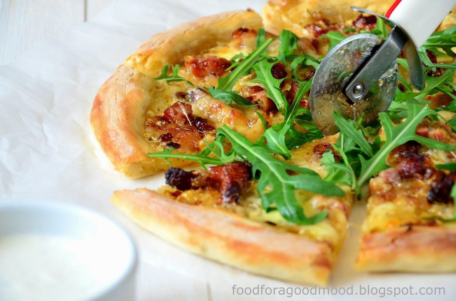 Gdy weźmiemy kawałek pizzy do ręki, sprężyste i cienkie ciasto wyraźnie ugnie się pod swoim ciężarem. To cecha idealnego spodu. A nadzienie? Biały sos, wiejski wędzony boczek, karmelizowana cebulka i mozzarella. Do tego garść rukoli niedbale rzucona na wierzch i mamy przepyszną domową pizzę, która tak naprawdę nie potrzebuje do towarzystwa żadnego sosu. Ten smak po prostu broni się sam!