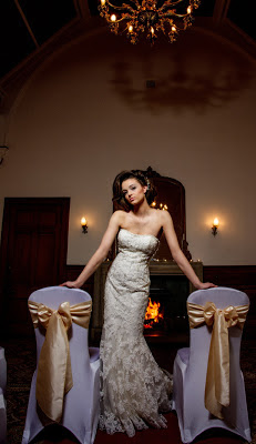 Bride in suptuous wedding dress standing in front of a roaring fire in the Newton Hotel, Nairn, Scotland