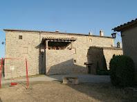 La façana nord-oest amb el porxo on hi ha el pou de la masia