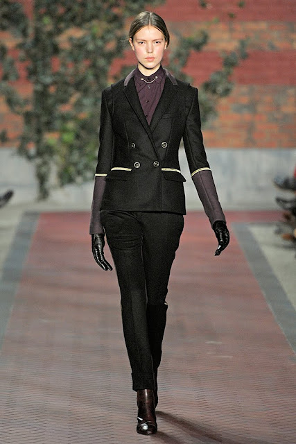 model from tommy hilfiger's fall rtw 2012 wearomg a black suit with trim piping