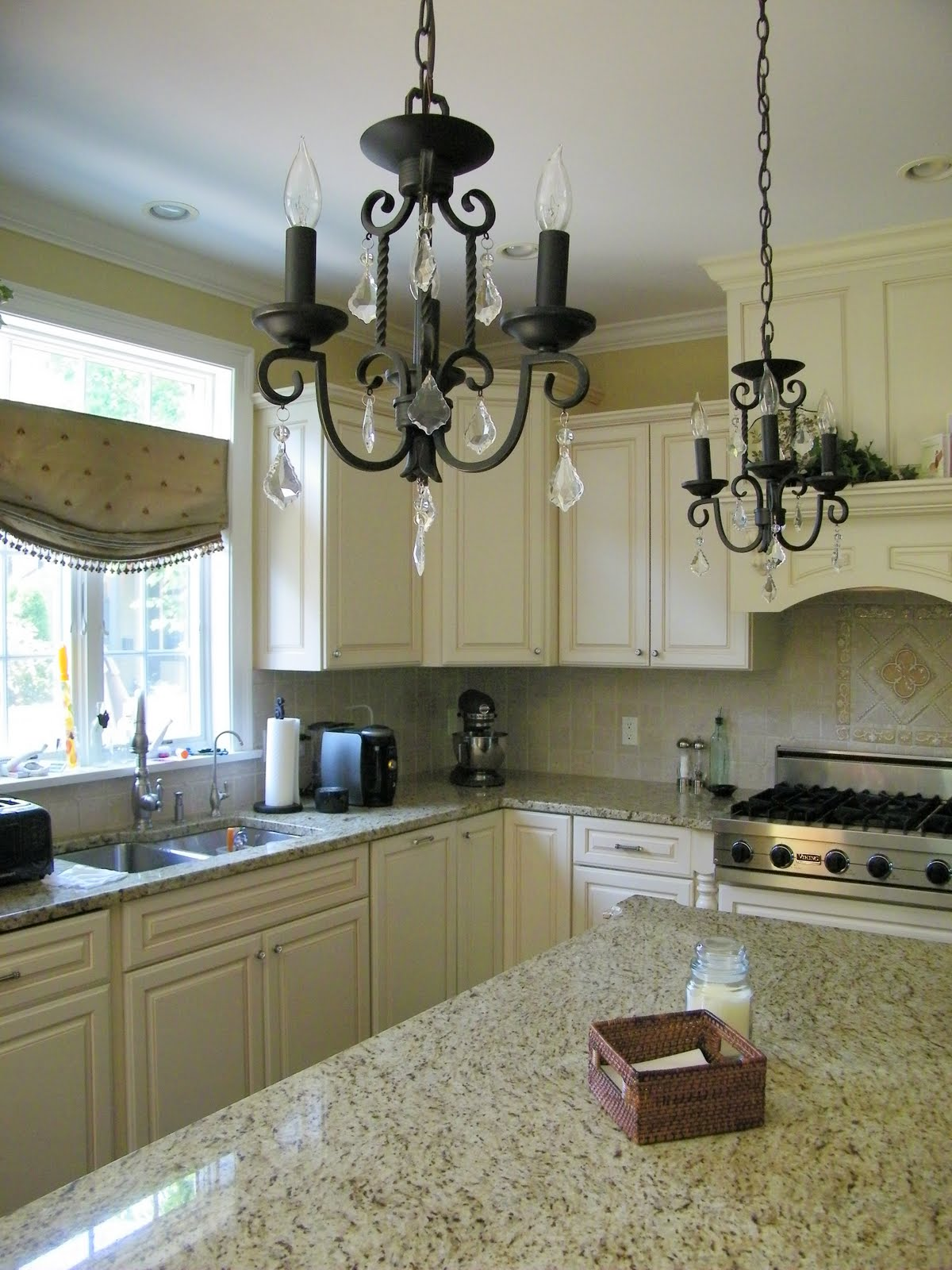 Double iron and crystal chandeliers and creamy ivory cabinets.