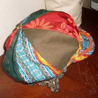 Rear side view of a eight-paneled crown hat with band around the edge and brim, all constructed from various fabrics in brown, two patterns of orange floral, green lace and blue-multi stripes. Accents include orange braided trim that follows the curve of the brim and a metal sunflower button at the top of the crown where the eight panels come together.