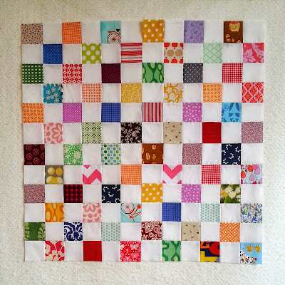 quilt blocks in a checker board pattern using a large variety of bright colors and prints