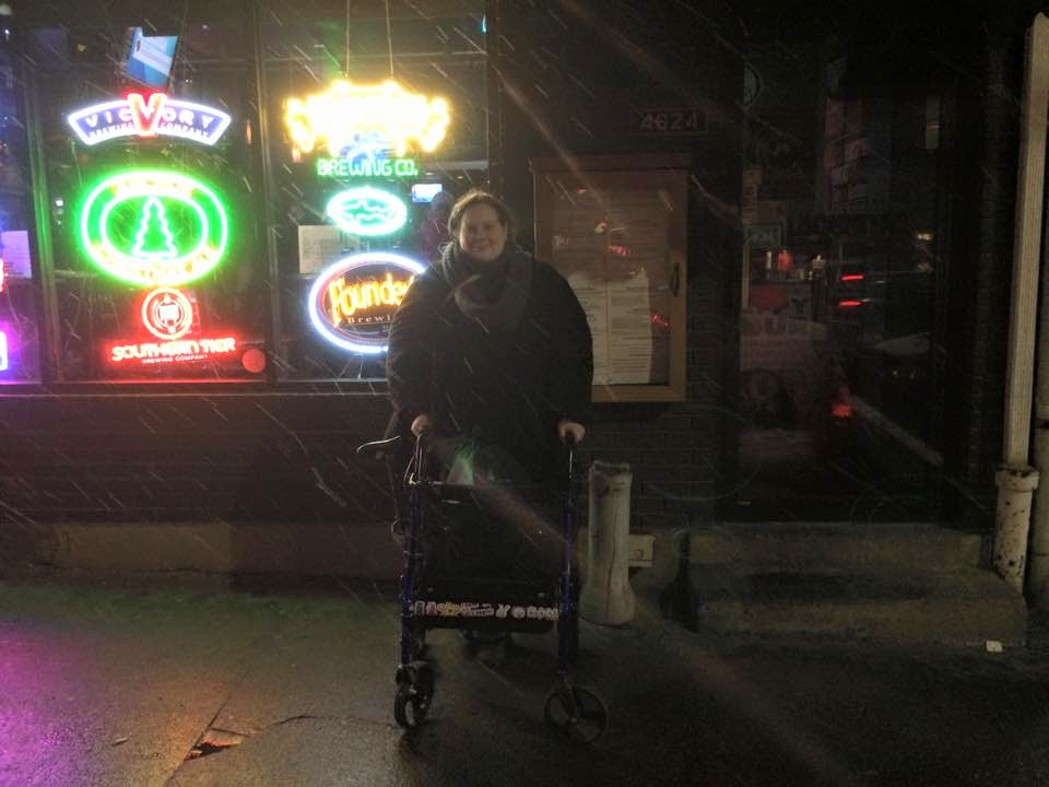 Photograph: A young dark-haired white woman in a coat and scarf holding onto a rollator walker outside of a bar in the snow. In the window several neon signs shine brightly.