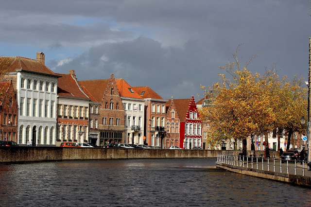 A canal in bruge on autumn day with grey sky and autumnal leaves