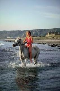 una mujer en bañador montada en un caballo