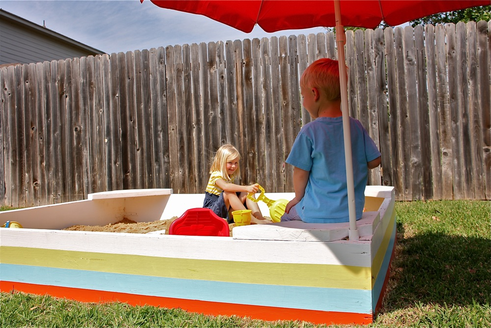 A Simple Backyard Sandbox With Colorful Stripes, Benches For Sitting,