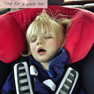 Toddler asleep in a car seat with mouth open